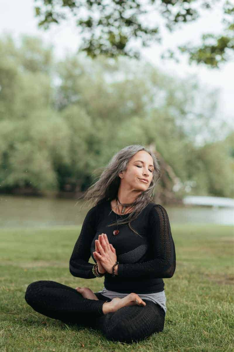 a woman sitting in a yoga pose wearing black workout clothes